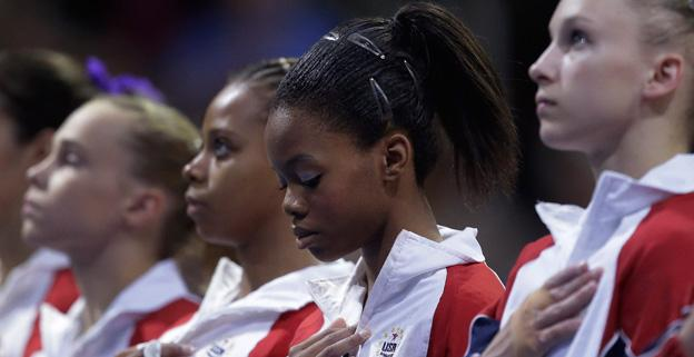 Gabby Douglas stands with other competitors during the playing of the national anthem during the final round of the women's Olympic gymnastics trials, Sunday, July 1.