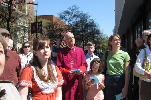 The Archbishop of Washington Donald Wuerl listens to part of a vigil for those abused by clergy members before going across the street to St. Matthew's Cathedral for Good Friday service.