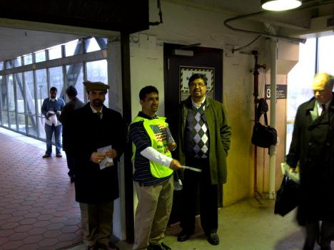 """A member of the Ahmadiyya Muslim Community passes out fliers as part of the """"Muslims for Loyalty"""" campaign."""