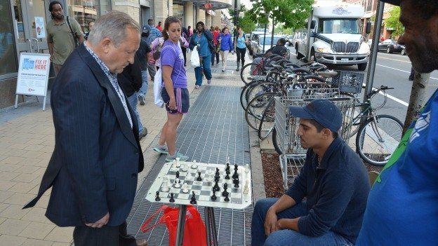Victor Savnkov and Jorge Belloso play chess on a makeshift board and table in Columbia Heights.
