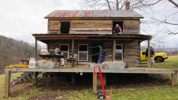 Volunteers begin deconstruction of the cabin in Hancock, Md. Wood siding covered the 135-year-old logs.