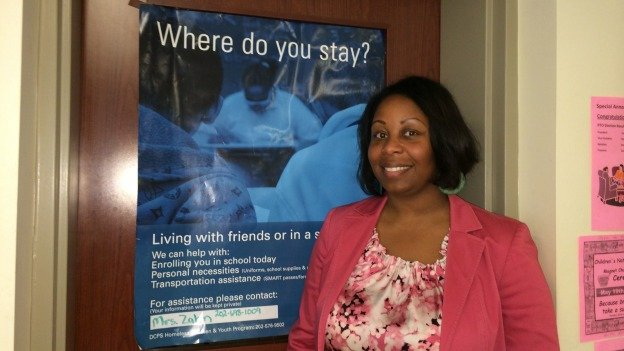 Principal Maisha Riddlesprigger standing in front of a poster advertising helping for homeless students.